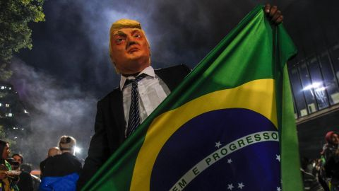 TOPSHOT - A supporter of far-right lawmaker and presidential candidate for the Social Liberal Party (PSL), Jair Bolsonaro, wears a mask of US President Donald Trump as he celebrates after Bolsonaro won Brazil's presidential election, in Sao Paulo, Brazil, on October 28, 2018. - Far-right former army captain Jair Bolsonaro was elected president of Brazil on Sunday, beating leftist opponent Fernando Haddad in a runoff election after a bitter and polarized campaign. Official results gave the controversial president-elect 55.18 percent of the vote with more than 99.7 percent of the ballots counted. (Photo by Miguel SCHINCARIOL / AFP)