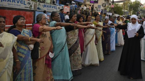 """Women raise their hands to take a pledge to fight gender discrimination as they form part of a hundreds kilometer long """"women's wall."""""""