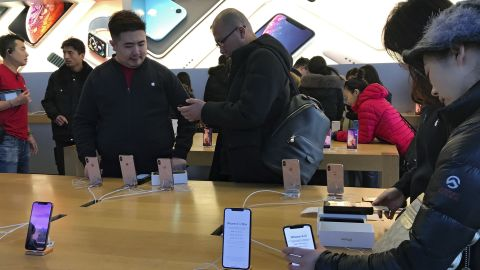 People buy latest iPhone while others try out its latest model at an Apple Store in Beijing, Tuesday, Dec. 11, 2018. China's economy czar and the U.S. Treasury secretary discussed plans for talks on a tariff battle, the government said Tuesday, indicating negotiations are going ahead despite tension over the arrest of a Chinese tech executive. (AP Photo/Andy Wong)