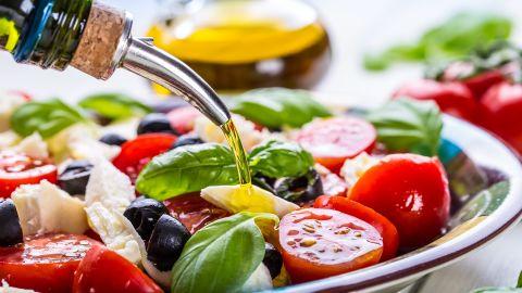 Caprese Italian or Mediterranean salad. Tomato mozzarella basil leaves black olives and olive oil on wooden table.; Shutterstock ID 291753935; Job: -