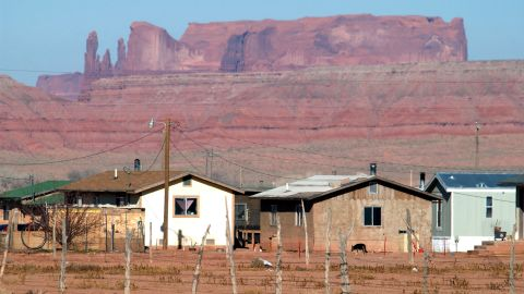 Houses are backed by sandstone cliffs on the Navajo reservation in Arizona.