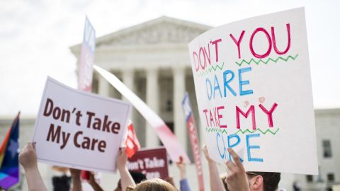 UNITED STATES - JUNE 25: Affordable Care Act supporters hold up signs outside the Supreme Court as they wait for the court's decision on Obamacare on Thursday, June 25, 2015. (Photo By Bill Clark/CQ Roll Call) (CQ Roll Call via AP Images)