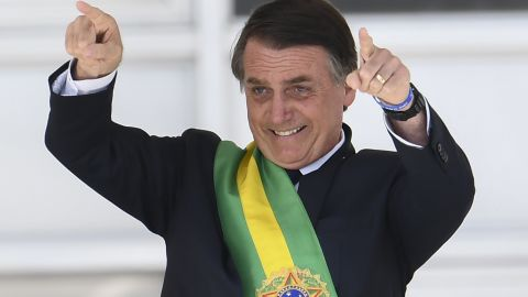 Brazil's new president Jair Bolsonaro gestures after receiving the presidential sash from outgoing Brazilian president Michel Temer (out of frame), at Planalto Palace in Brasilia on January 1, 2019. - Bolsonaro takes office with promises to radically change the path taken by Latin America's biggest country by trashing decades of centre-left policies. (Photo by EVARISTO SA / AFP)        (Photo credit should read EVARISTO SA/AFP/Getty Images)