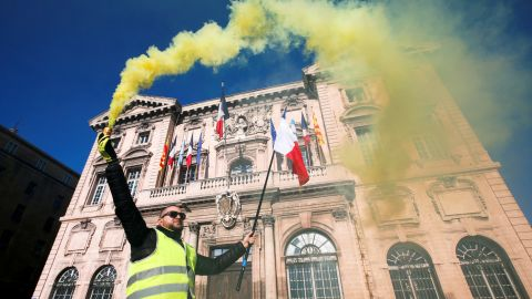 A protester in Marseille holds a flare in front of the town hall.