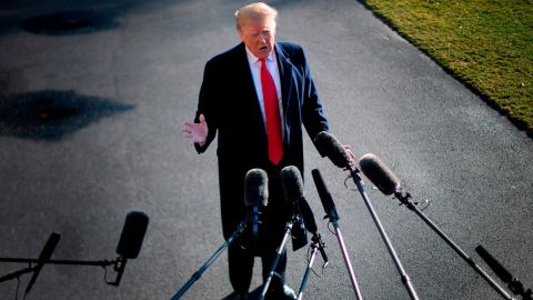 """US President Donald Trump speaks to the press as he departs the White House in Washington, DC, on January 6, 2019, for meetings at Camp David. - President Donald Trump stood firm Sunday on his demand for billions of dollars to fund a border wall with Mexico, which has forced a shutdown of the US government now entering its third week.""""We have to build the wall,"""" Trump told reporters as he left the  White House for the Camp David presidential retreat, while  conceding that the barrier could be """"steel instead of concrete."""" (Photo by Jim WATSON / AFP)        (Photo credit should read JIM WATSON/AFP/Getty Images)"""