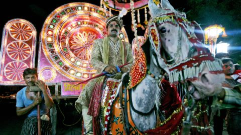 An Indian groom rides a horse on his way to his bride's house for their wedding ceremony.