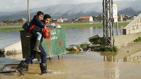 A teenager carries a boy across a flooded street near a Syrian refugee camp.