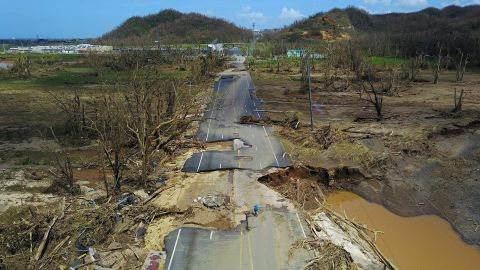 TOPSHOT - A man rides his bicycle through a damaged road in Toa Alta, west of San Juan, Puerto Rico, on September 24, 2017 following the passage of Hurricane Maria.Authorities in Puerto Rico rushed on September 23, 2017 to evacuate people living downriver from a dam said to be in danger of collapsing because of flooding from Hurricane Maria. / AFP PHOTO / Ricardo ARDUENGO        (Photo credit should read RICARDO ARDUENGO/AFP/Getty Images)