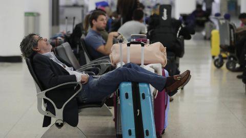 A traveler sleeps near a closed terminal at Miami International Airport on January 12.