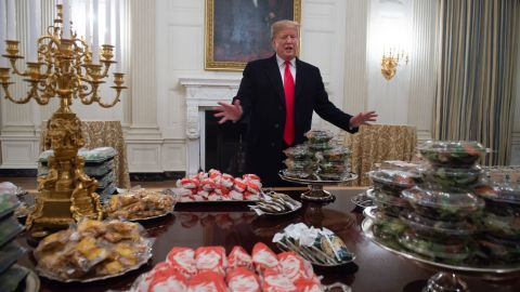 """Trump displays <a href=""""https://www.cnn.com/2019/01/14/politics/donald-trump-clemson-food/index.html"""" target=""""_blank"""">fast food </a>for Clemson University's football team to celebrate its national championship at the White House on January 14. The administration said Trump paid for the meal after much of the White House residence staff, including chefs, were furloughed."""