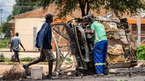 """Scrap metal collectors salvages sellable parts from a car shell burnt during the three days protests in Emakhandeni township, in Bulawayo, on January 17, 2019. - Nationwide demonstrations erupted on January 14 following a crippling strike over the increase in the price of fuel announced by Zimbabwean President to tackle a shortfall caused by increased demand and """"rampant"""" illegal trading. (Photo by ZINYANGE AUNTONY / AFP)        (Photo credit should read ZINYANGE AUNTONY/AFP/Getty Images)"""