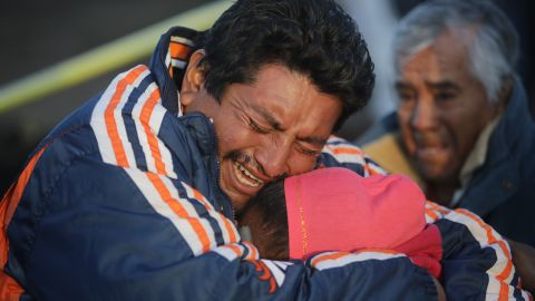 Relatives cry after recognizing the body of a loved one in the deadly pipeline blast on Saturday, January 19.