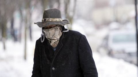 Marvin Hooks wears a face mask to protect him from the cold as he walks on North Street in Pittsfield, Mass., Monday, Jan. 21, 2019. Bitter cold and gusty winds swept across the eastern U.S. Monday with falling temperatures replacing the weekend's falling snow. (Ben Garver/The Berkshire Eagle via AP)