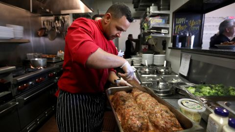 Chef Joshua Wiggins cuts portions of meatloaf for furloughed federal workers in Red Bank, New Jersey, on Monday, January 21. The free lunch was served at JBJ Soul Kitchen, the restaurant of rock star Jon Bon Jovi.
