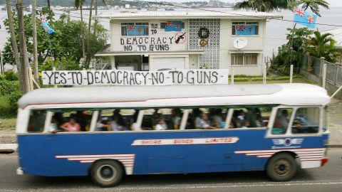 A bus passes by a house covered with anti-coup banners near Suva, the capital of Fiji, on December 6, 2006. Critics of the new law fear it could restore censorship.