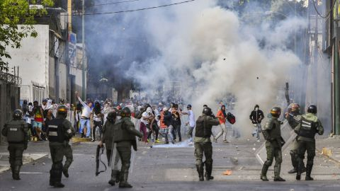 """TOPSHOT - Riot police clash with opposition demonstrators during a protest against the government of President Nicolas Maduro on the anniversary of the 1958 uprising that overthrew the military dictatorship, in Caracas on January 23, 2019. - Venezuela's National Assembly head Juan Guaido declared himself the country's """"acting president"""" on Wednesday during a mass opposition rally against leader Nicolas Maduro. (Photo by YURI CORTEZ / AFP)        (Photo credit should read YURI CORTEZ/AFP/Getty Images)"""