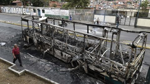 A man walks by a bus that had been set on fire in Caracas.