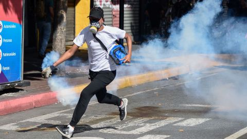 An opposition demonstrator runs with a tear-gas canister on January 23.