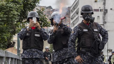 A National Police officer fires tear gas at demonstrators in Caracas while another shoots the scene with a cell phone.