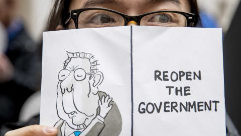 """A furloughed worker displays a sign that reads """"Reopen the Government"""" during a protest in Washington on January 23."""