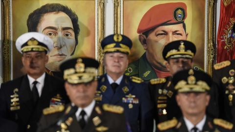 Portraits of former Venezuelan leaders Simon Bolivar and Hugo Chavez hover in the background as Venezuelan Defense Minister Vladimir Padrino Lopez, bottom left, addresses a news conference in Caracas on Thursday, January 24. Venezuela's top military officials swore their allegiance to Maduroafter other nations recognized Guaido as head of state.