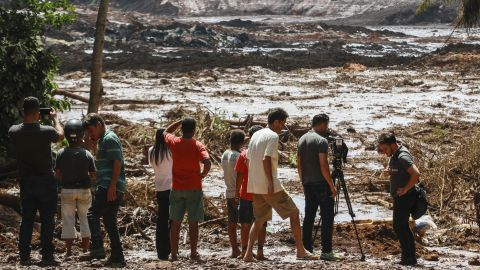 People observe the mud masses Friday after the break of the dam at the Feijao mine.