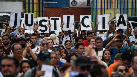 """Supporters of Venezuela's opposition hold up letters that read """"Justice"""" at a rally to hear Guaido speak in Caracas on Saturday, January 26."""