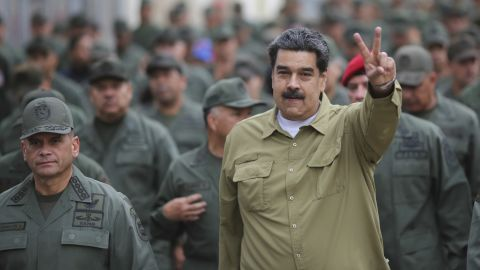 """In this handout photo released by the Miraflores Presidential Press Office, Maduro flashes a """"V for victory"""" hand gesture after arriving at the Fort Tiuna military base in Caracas on January 30."""