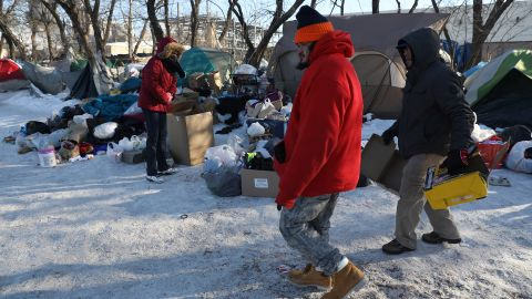 Felipe, center, and George Arroyo, right, look for carton boxes to burn inside a garbage can to keep an improvised fire going at a makeshift camp on Roosevelt Road near the Dan Ryan Expressway on Jan 30, 2019. (Abel Uribe/Chicago Tribune/TNS via Getty Images)