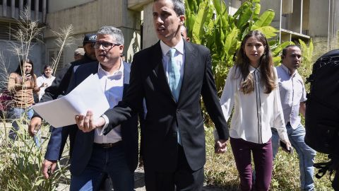 """Opposition leader and self-proclaimed """"acting president"""" Juan Guaido (C) accompained by his wife Fabiana Rosales (2-R) arrives at Venezuela's Central University (UCV) in Caracas to present his government's plan on January 31, 2019. - Venezuela's self-proclaimed acting president Juan Guaido ruled out the possibility of civil war in his country, saying the overwhelming majority of his compatriots wanted Nicolas Maduro to step down. In an interview to Spain's El Pais newspaper published Thursday, Guaido repeated an appeal to Venezuela's armed forces to take his side. (Photo by JUAN BARRETO / AFP)        (Photo credit should read JUAN BARRETO/AFP/Getty Images)"""