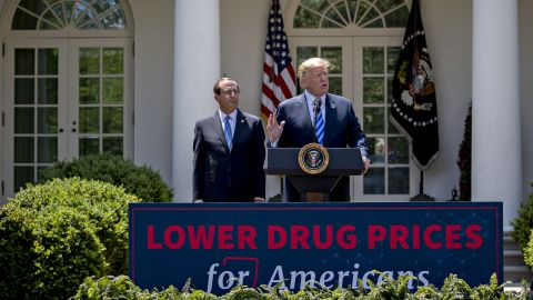 U.S. President Donald Trump, right, speaks as Alex Azar, secretary of Health and Human Services (HHS), listens during an event on lowering drug prices in the Rose Garden of the White House in Washington, D.C., U.S., on Friday, May 11, 2018. Trump is proposing a sweeping effort to bring down U.S. drug prices in a long-awaited plan meant to fulfill a promise he has been pushing since his bid for the White House. Photographer: Andrew Harrer/Bloomberg via Getty Images