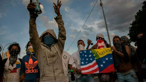 Anti-government protesters prepare to sing Venezuela's national anthem while blocking a highway in Caracas on February 2, 2019.