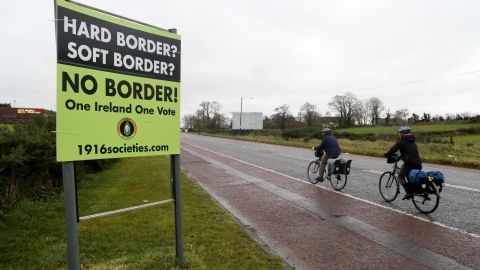 """Cyclists pass a sign calling for no border to be imposed between Ireland and Northern Ireland outside Newry, Northern Ireland, on November 14, 2018 near the Irish border. - British Prime Minister Theresa May defended her anguished divorce deal with the European Union before rowdy lawmakers on Wednesday before  trying to win the backing of her splintered cabinet with the so-called """"Irish backstop"""" arrangement to guard against the imposition of a hard border between Ireland and Northern Ireland one of the contentious issues, according to reports. (Photo by Paul FAITH / AFP)        (Photo credit should read PAUL FAITH/AFP/Getty Images)"""