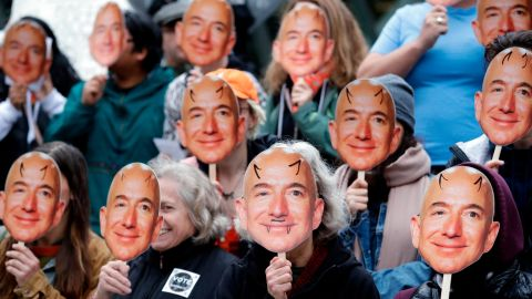 """Demonstrators hold images of Amazon CEO Jeff Bezos near their faces during a Halloween-themed protest at Amazon headquarters over the company's facial recognition system, """"Rekognition,"""" Wednesday, Oct. 31, 2018, in Seattle. Protesters said that they were there in support of hundreds of Amazon employees who have signed a letter asking the company to stop marketing their facial recognition software to ICE and to drop its contract with software company Palantir and to law enforcement agencies. (AP Photo/Elaine Thompson)"""