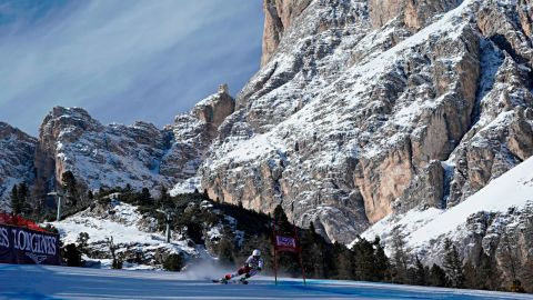 A female skier competes against the domineering backdrop of Cortina's rocky mountains.