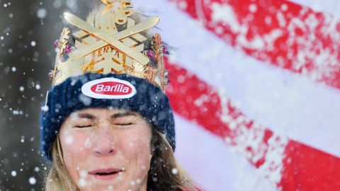 Mikaela Shiffrin closes her eyes as her runners-up celebrate by throwing snowballs at her in Kronplatz.