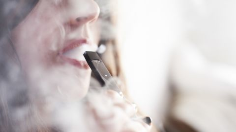 A person smokes a Juul Labs Inc. e-cigarette in this arranged photograph taken in the Brooklyn Borough of New York, U.S., on Sunday July 8, 2018. Juul Labs, the maker of the popular e-cigarette brand that has recently come under fire from health officials over its popularity with young adults, plans to introduce a line of lower-nicotine pods. The company will begin to sell pods with a 3-percent nicotine concentration in its mint and Virginia tobacco flavors later this year, according to a statement Thursday. Photographer: Gabby Jones/Bloomberg via Getty Images