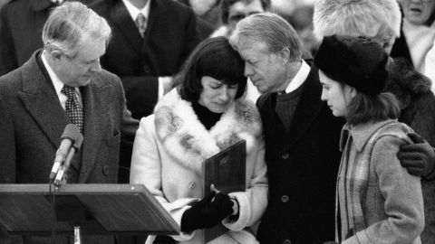 President Jimmy Carter comforts Mary Anne Dubs, widow of slain Ambassador Adolph Dubs, as Dubs' body is returned to Andrews Air Force Base on February 18, 1979. At right is the ambassador's daughter, Lindsay.