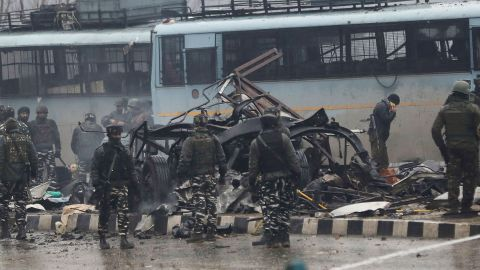 Indian security forces inspect the scene of an attack on a paramilitary convoy.