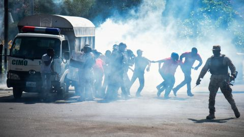 Haitian people run from teargas fired by policeman during clashes with demonstrators near the National Palace, in the centre of Haitian Capital Port-au-Prince, February 13, 2019, on the seventh day of protests against Haitian President Jovenel Moise and the misuse of the Petrocaribe fund. (Photo by HECTOR RETAMAL / AFP)        (Photo credit should read HECTOR RETAMAL/AFP/Getty Images)