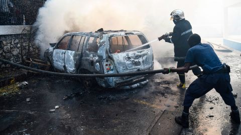 Fireman extinguish burning cars at the offices of Television Nationale d'Haiti in the Haitian Capital Port-au-Prince, February 13, 2019, on the seventh day of protests against Haitian President Jovenel Moise and the misuse of the Petrocaribe fund. (Photo by HECTOR RETAMAL / AFP)        (Photo credit should read HECTOR RETAMAL/AFP/Getty Images)