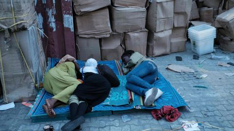 Staff of the Independent National Electoral Commission (INEC) sleep on a ground beside electoral items at a local office in Port Harcourt, Southern Nigeria on February 16, 2019 after Nigeria's electoral watchdog postponed presidential and parliamentary elections for one week, just hours before polls were due to open. - The two main political parties swiftly condemned the move and accused each other of orchestrating the delay as a way of manipulating the vote. (Photo by Yasuyoshi CHIBA / AFP)
