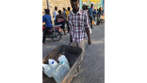 One man carries jugs of water he received from a private resident.