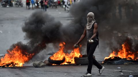 TOPSHOT - A demonstrator walks past next to barricades during clashes with Haitian police, in Port-au-Prince, on February 15, 2019, on the ninth day of protests against Haitian President Jovenel Moise and the misuse of the Petrocaribe fund. - Since February 7, at least seven people have died as Haiti has been plunged into political crisis, with everyday life paralyzed by protests and barricades in the largest towns. (Photo by HECTOR RETAMAL / AFP)        (Photo credit should read HECTOR RETAMAL/AFP/Getty Images)