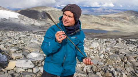 In Norway, archaeologists from a program called Secrets of the Ice are searching for items that melt out of ice patches. Pictured, a team member holds a 1,400-year-old arrow.