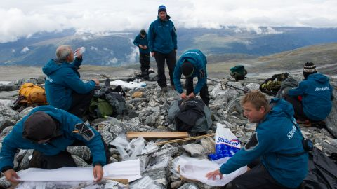 Glacial archaeologists pack artifacts after a day of fieldwork in a glaciated mountain pass.