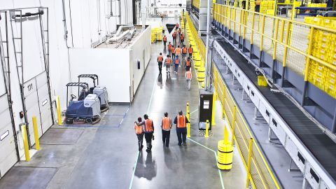 FILE -- Workers at an Amazon warehouse in Carteret, N.J., Aug. 30, 2017. The e-commerce giant has won two patents for a tracking technology that can nudge a human hand in the right direction -- toward a warehouse bin, say. (Bryan Anselm/The New York Times)