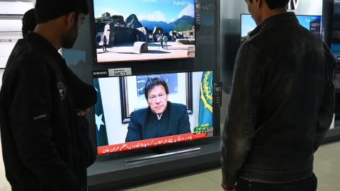 Pakistani people watch the television in Islamabad on February 19 as Prime Minister Imran Khan speaks to the population about the attack in Indian-administered Kashmir on February 14.