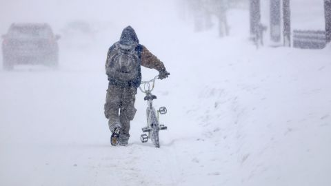 Austin Tauber walks his bicycle through heavy snow in Anoka, Minnesota, on Wednesday.