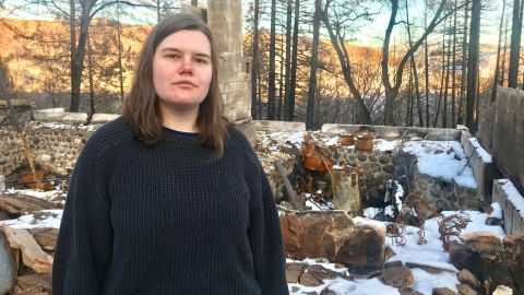 Sarah Peters stands in front of her destroyed home in Paradise, California.